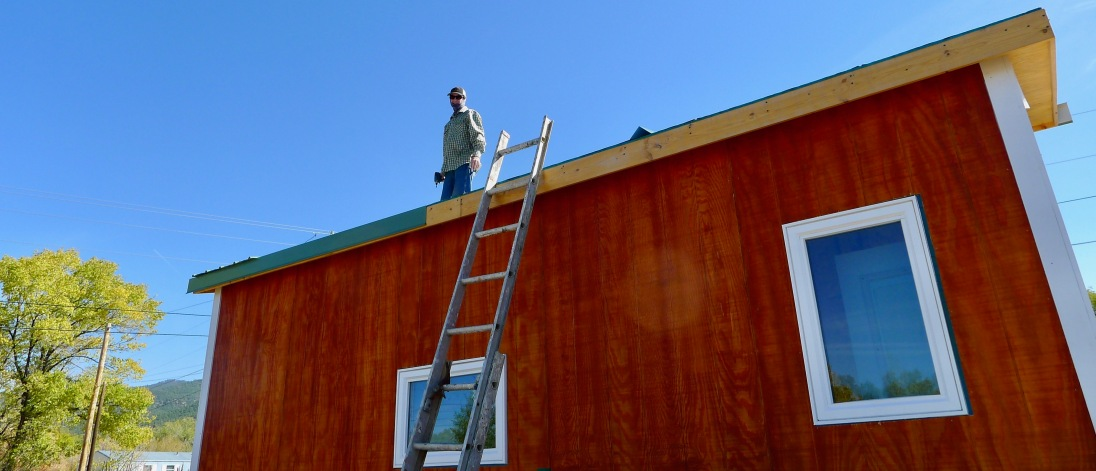 Brad preparing to install the second row of metal roof panels.